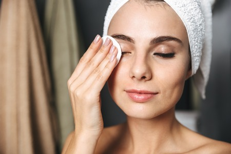 Beautiful young woman wrapped in bath towel standing at the bathroom, removing makeup with a cotton pad Stock Photo