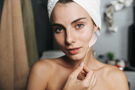 Close up of a beautiful young girl with towel wrapped around her head touching her skin with a feather at the bathroom