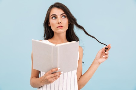 Image of thinking young woman posing isolated over blue background wall holding book reading.