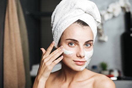 Beautiful young woman with towel wrapped around her head applying face mask at the bathroom Фото со стока