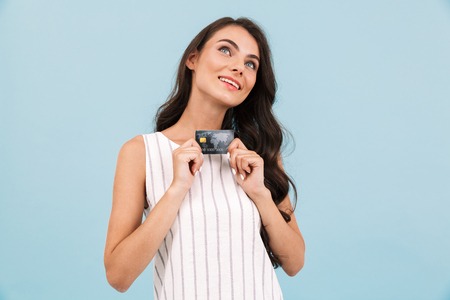 Bild der erstaunlichen jungen Frau, die lokalisiert über der blauen Hintergrundwand aufwirft, die Kreditkarte hält.