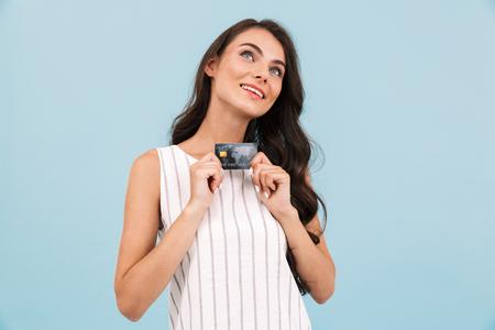 Immagine di stupefacente giovane donna in posa isolato su sfondo blu parete in possesso di carta di credito.