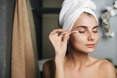 Pretty young woman with towel on head removing makeup with a cotton swab in front of mirror in bathroom