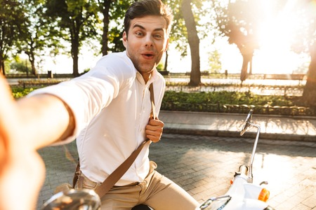 Photo of a handsome shocked excited young business man walking outdoors on scooter take a selfie by camera.