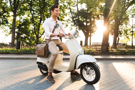Image of a handsome young business man walking outdoors on scooter.
