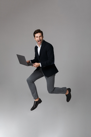 Full length image of caucasian businessman 30s in suit rejoicing while using laptop isolated over gray background