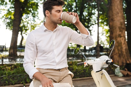Happy young businessman sitting on a motorbike outdoors, reading newspaper, drinking coffee