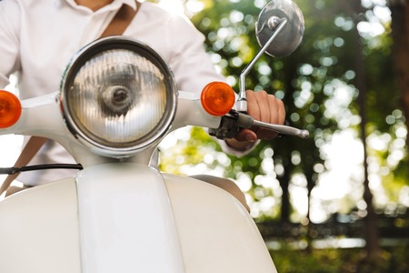 Cropped image of a young businessman sitting on a motorbike outdoors