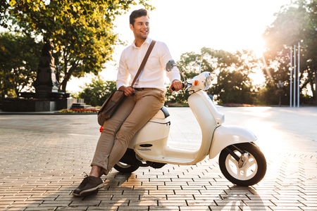 Happy young businessman sitting on a motorbike outdoors, looking away