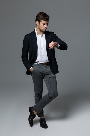 Full length portrait of a handsome young businessman dressed in suit isolated over gray background, posing, checking time