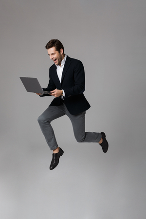 Full length image of successful businessman 30s in suit rejoicing while using laptop isolated over gray background Stock Photo