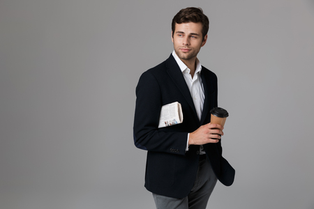Image of caucasian man 30s in formal suit holding coffee and newspaper isolated over gray background