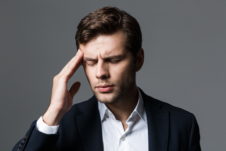 Close up portrait of a exhausted young businessman dressed in suit isolated over gray background, suffering from a headache
