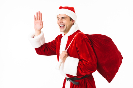 Portrait of caucasian man 30s in santa claus costume and red hat walking with gift bag over shoulder isolated on white background in studio