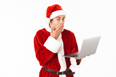 Portrait of a cheerful young man dressed in santa claus costume standing isolated over white background, holding laptop computer Stock Photo