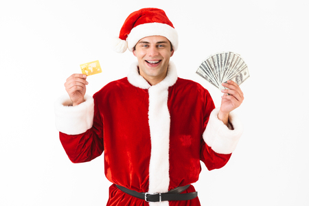 Image of happy man 30s in santa claus costume holding dollar bills and credit card isolated on white background in studio