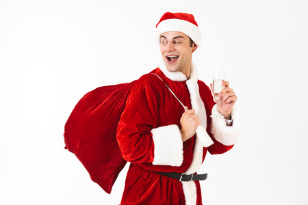 Portrait of optimistic man 30s in santa costume and red hat holding gift bag and glass with champagne isolated on white background in studio Stock Photo