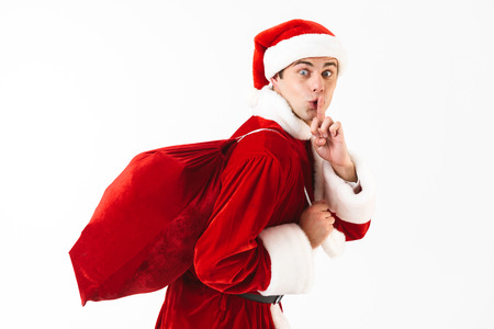 Portrait of young man 30s in santa claus costume and red hat walking with gift bag over shoulder isolated on white background in studio Stock Photo