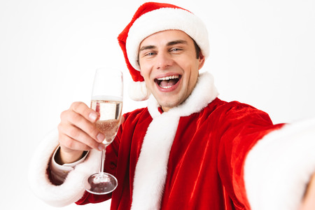 Portrait of handsome man 30s in santa claus costume and red hat taking selfie photo while holding glass with champagne isolated over white background in studio