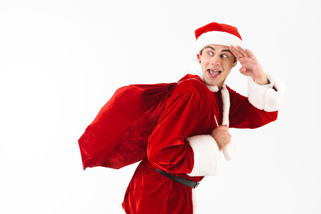 Portrait of optimistic man 30s in santa claus costume and red hat running with gift bag over shoulder isolated on white background in studio