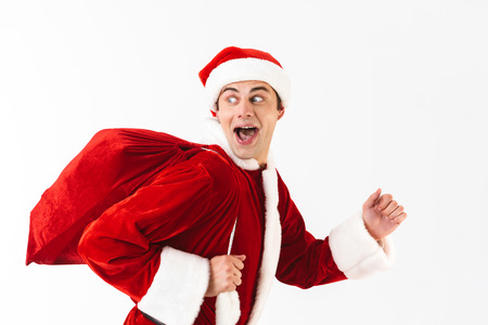 Portrait of positive man 30s in santa claus costume and red hat running with gift bag over shoulder isolated on white background in studio