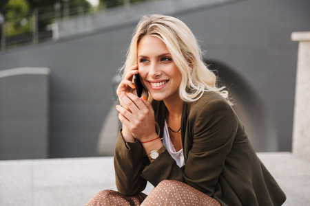Image of happy woman 20s talking on smartphone while sitting on concrete parapet outdoor