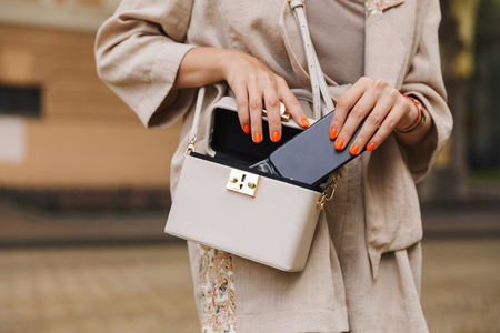 Cropped photo of young woman walking outdoors put her mobile phone to bag. Reklamní fotografie
