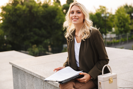 Image of charming woman smiling and holding paper folder while sitting on concrete parapet outdoor