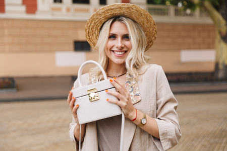 Image of elegant lady wearing suit and straw hat showing her stylish purse while walking through city street
