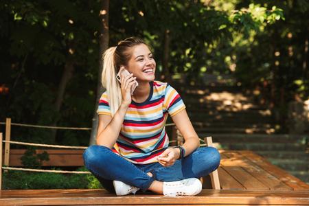 Retrato de una sonriente joven adolescente sentado en un banco en el parque, hablando por teléfono móvil