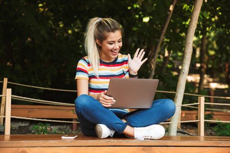 Portrait of an excited young teenage girl sitting on a bench at the park, using laptop computer on her lap 免版税图像