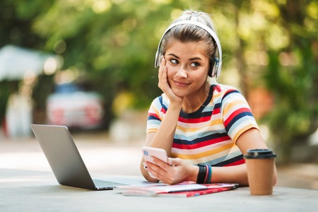 Portrait of a smiling young teenage girl sitting at the table at the park, listening to music with headphones, using mobile phone Archivio Fotografico