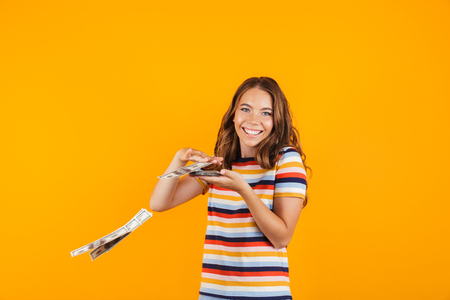 Portrait of a smiling cheerful young girl standing isolated over yellow background, throwing away money banknotes