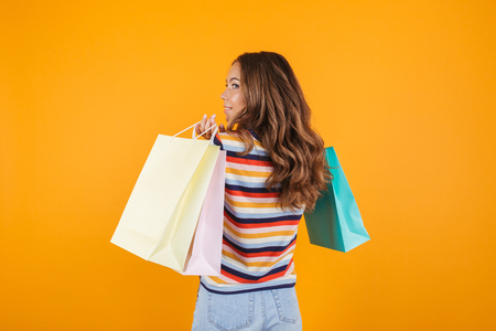 Back view image of a happy young girl posing over yellow wall background holding shopping bags. Banque d'images - 113307826
