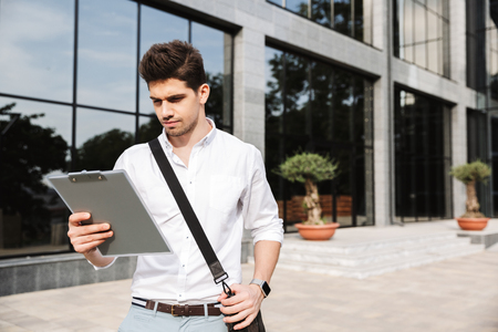 Confident successful young businessman dressed white shirt working outdoors, holding tablet, noting