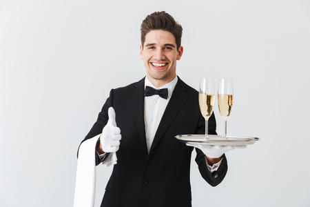 Portrait of a smiling young waiter in tuxedo offers you glass of champagne over white background, giving thumbs up Foto de archivo - 113308055