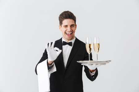 Portrait of a smiling young waiter in tuxedo offers you glass of champagne over white background Foto de archivo - 113308418