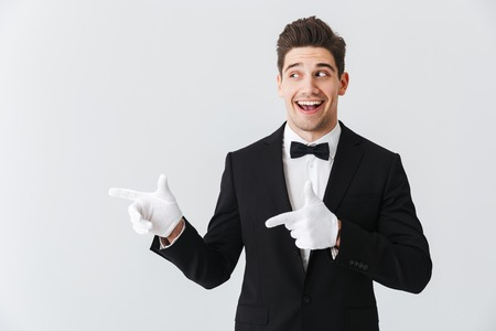 Portrait of a handsome young man waiter wearing tuxedo and gloves standing isolated over white background, pointing fingers at copy space