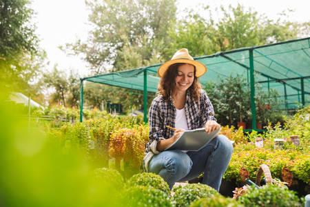 Attractive beautiful woman gardener working near flowers in greenhouse writing notes