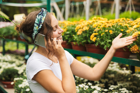 Cheerful young woman gardener talking on mobile phone while standing inside a greenhouse