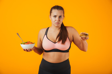 Portrait of an upset overweight fitness woman wearing sports clothing standing isolated over yellow background, holding bowl with salad and a burger Stock Photo