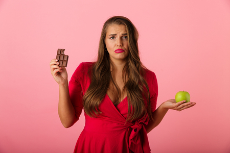 Image of a sad young woman isolated over pink wall background holding chocolate and apple.