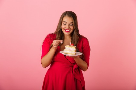 Image of an excited hungry young woman isolated over pink wall background holding cake.