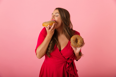 Image of an excited young woman isolated over pink wall background eat donuts. Stock Photo