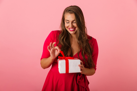 Photo of beautiful chubby woman 20s wearing red dress smiling and holding gift box isolated over pink background Stock Photo