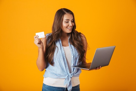 Portrait of a happy young casual woman standing isolated over yellow background, holding laptop computer, showing plastic credit card Stock Photo