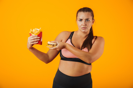 Image of displeased overweight woman in tracksuit doing stop gesture while holding sandwich and french fries isolated over yellow background