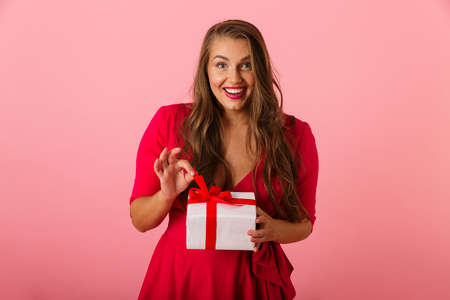 Photo of excited chubby woman 20s wearing red dress smiling and holding present box isolated over pink background