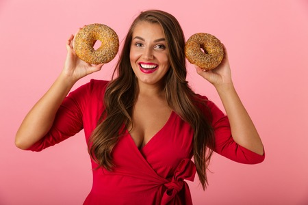 Image of a happy young woman isolated over pink wall background holding donuts.