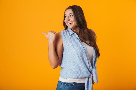 Heureuse jeune femme debout isolée sur fond jaune, pointant le doigt loin